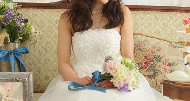 青いリボンの付いたブーケを持っている花嫁